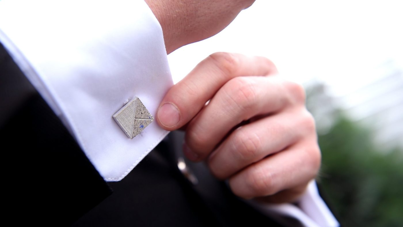 Concrete Cufflink blue-white being adjusted by a suited man